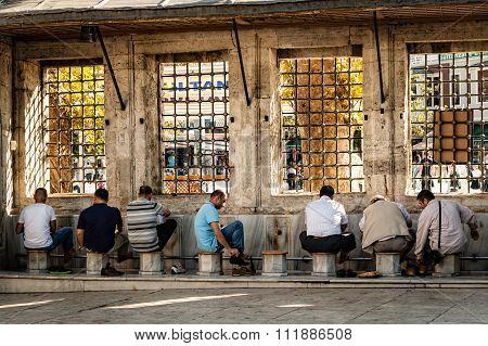 Men Washing Their Feet Outside A Mosque.