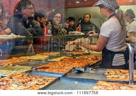 ALBA, ITALY - NOVEMBER 15, 2015: People inside typical pizzeria bying pizza - traditional italian dish invented in Naples, very popular in all over the world.