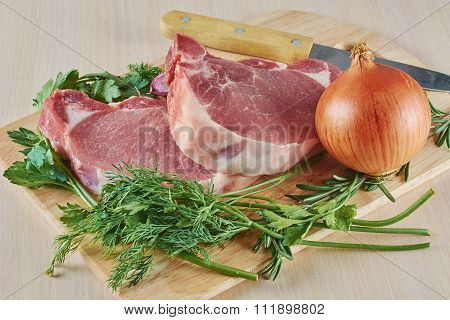 Pork Stake Onions And Greens On A Board