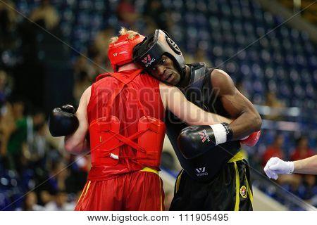JAKARTA, INDONESIA - NOVEMBER 18, 2015: Dmytro Batok of Ukraine (red) fights Xavier Foupapokam of France (black) in the men's 85kg Sanda event at the 13th World Wushu Championship 2015.