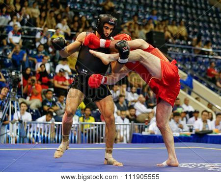 JAKARTA, INDONESIA - NOVEMBER 18, 2015: Ali Abdulkhalikov of Russia (red) fights Ayman Mohamed of Eygpt (black) in the men's 75kg Sanda event at the 13th World Wushu Championship 2015.