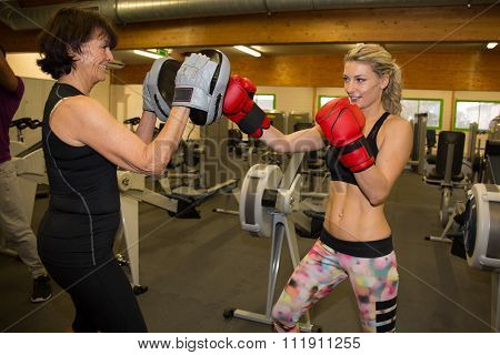 Two Female Boxer With Fighting Stance Against Fitness Center