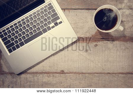 Work desk with laptop computer and hot coffee cup. Top view rustic wooden table background with copy space in vintage toned.