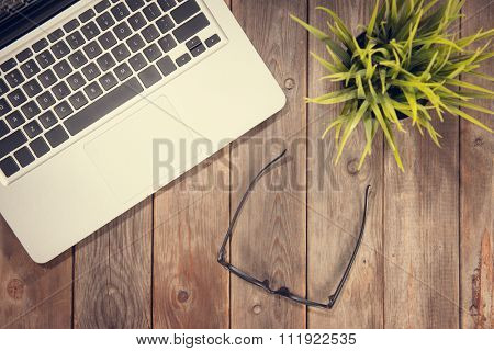 Top view working desk with laptop computer, eyeglasses and plant pot. Instant photo vintage split toning color effect.