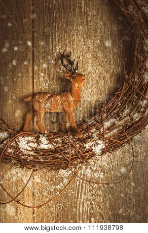 Reindeer figure sitting on garland with falling snow for the Christmas season