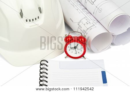 Blueprint rols and helmet with alarm clock