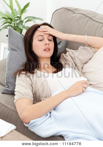 Sick Woman Lying On The Sofa And Touching Her Forehead