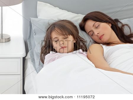 Cute little girl sleeping with her mother in the morning at home poster