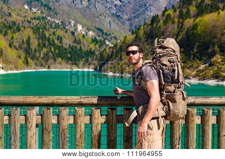 Beard hiker with backpack at the lakeside in dolomiti bellunesi national park looking at camera poster