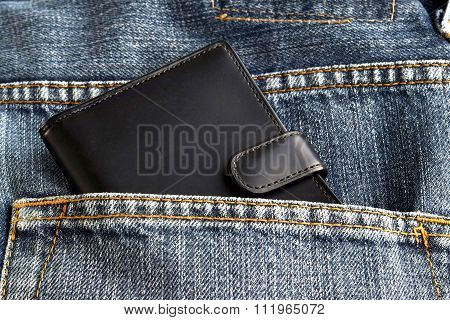 Black wallet in jeans trousers back pocket