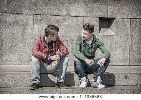 Two young men talking while sitting on curb