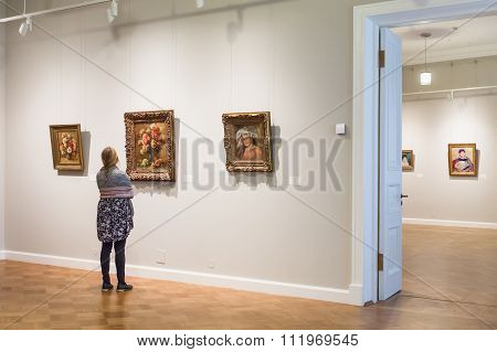 The Girl Is Looking At Impressionist Paintings Auguste Renoir At The Museum Of The Hermitage, St. Pe