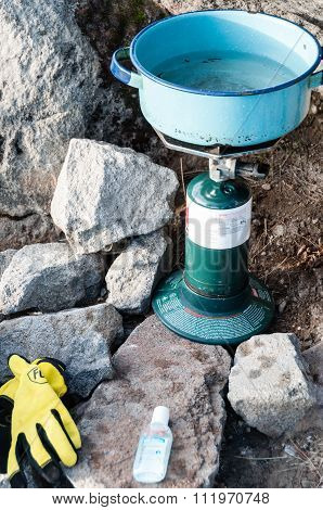 Boiling Water with camping stove amidst big Rocks and stones in The Mountain Tajamulco