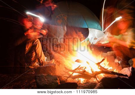 Hikers Gathered Around a campfire at night with long exposure shot