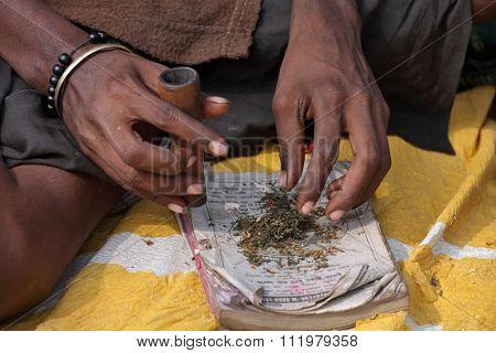 ALLAHABAD, INDIA - FEBRUARY 07, 2013: Sadhu is preparing his chillum to smoke ganja (marihuana)