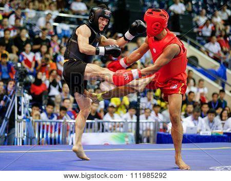 JAKARTA, INDONESIA - NOVEMBER 18, 2015: Yusuf Widiyanto of Indonesia (red) fights Van Bau To of Vietnam (black) in the men's 56kg Sanda final event at the 13th World Wushu Championship 2015.