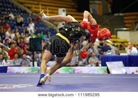 JAKARTA, INDONESIA - NOVEMBER 18, 2015: Seungmo Park of South Korea (red) fights Ji Fu Xu of China (black) in the men's 65kg Sanda final event at the 13th World Wushu Championship 2015.