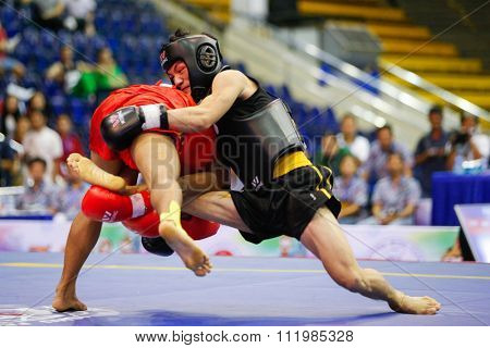 JAKARTA, INDONESIA - NOVEMBER 18, 2015: Yusuf Widiyanto of Indonesia (red) fights Van Bau To of Vietnam (black) in the men's 56kg Sanda final event at the 13th World Wushu Championship 2015.