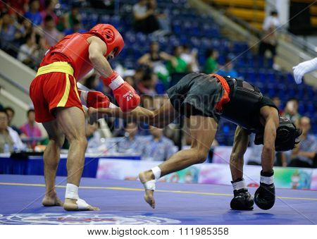 JAKARTA, INDONESIA - NOVEMBER 18, 2015: Uchit Sharma of India (red) fights Arnel Mandal of Philippines (black) in the men's 52kg Sanda final event at the 13th World Wushu Championship 2015.