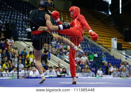 JAKARTA, INDONESIA - NOVEMBER 18, 2015: Shahrbano Semiromi of Iran (red) fights Hergie Bacyadan of Philippines (black) in the women's 65kg Sanda final event at the 13th World Wushu Championship 2015.