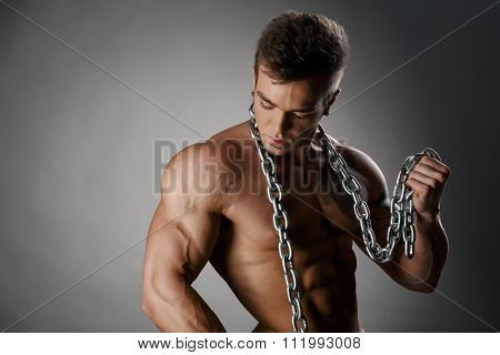Portrait of tanned bodybuilder posing with chain