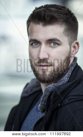 Portrait of young sympathetic man with a beard