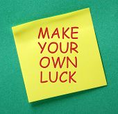 The message Make Your Own Luck in red text on a yellow sticky note posted on a green notice board as a reminder poster