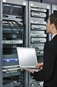 young engeneer business man with thin modern aluminium laptop in network server room poster