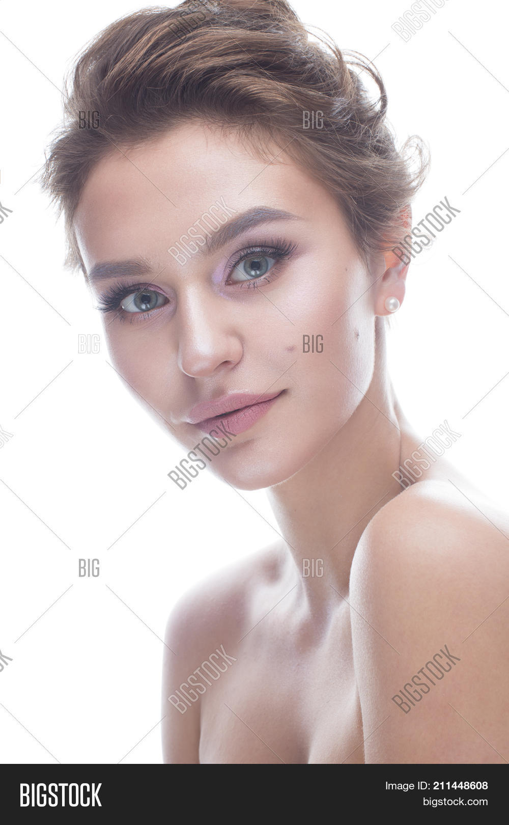 Young girl with a gentle nude makeup and hairstyle. Beautiful model with  shining perfect skin