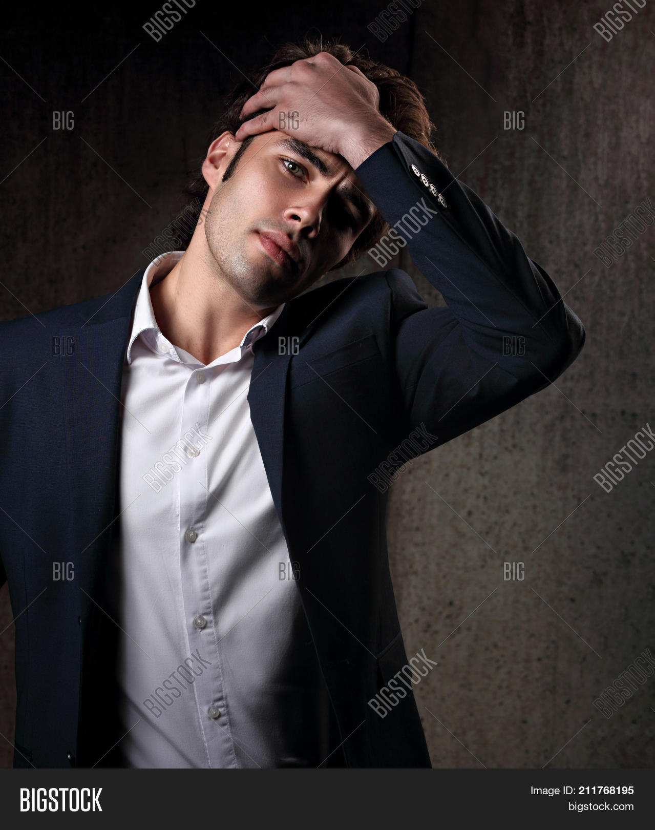 0968680e Charismatic handsome male model posing in blue fashion suit and white style  shirt looking on dark shadow background. Closeup portrait