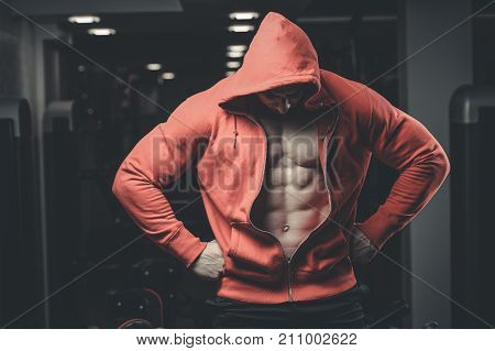 Handsome young muscular Caucasian man of model appearance posing in the gym gaining weight pumping up muscles and poses fitness and bodybuilding concept