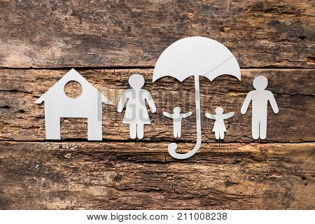 Silhouettes Of A Family Of Paper Under Umbrellas Near The House - The Concept Of Protection And Insu
