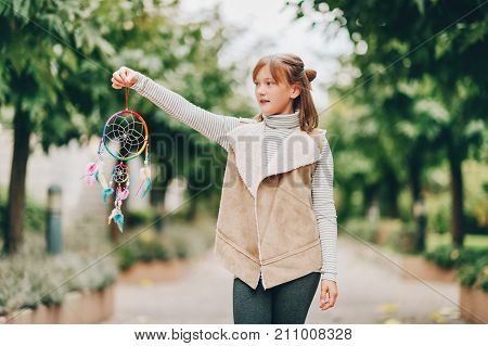 Outdoor portrait of adorable preteen kid girl holding colorful dream catcher wearing stripe roll neck and leather jacket