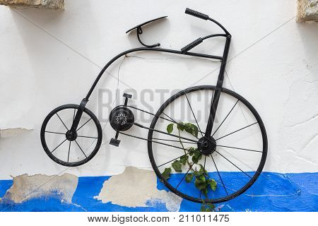 Hstorical Vintage Velocipede Bicycle Hanging on Street Wall.