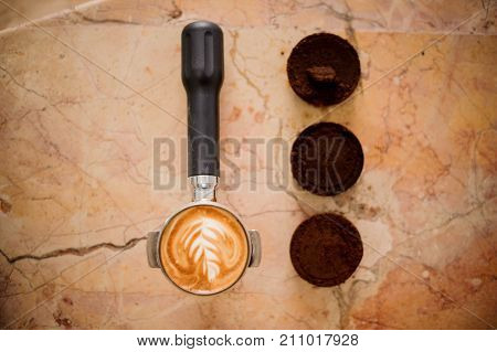 Baristas temper with beautiful latte art and three coffee tablets arranged on the bright surface