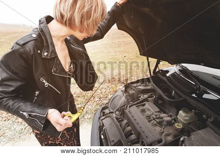 The blonde girl opens the hood of her car and checks the engine oil level. The concept of car maintenance by women. The concept of a malfunction of the car and its engine