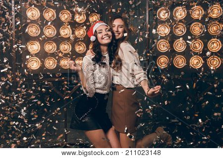 Two happy beautiful girls in Santa's hat with bengal lights dancing and have a fun in gold and silver confetti. Christmas party with my best friend. New Year 2018