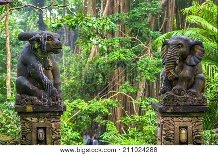 The traditional stone mythical elephant and ox figure are soiled with a bird's litter in the rainforest against the background of a branch and tall trees. Monkey Forest, Ubud, Bali, Indonesia.
