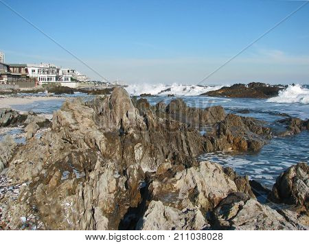 WINTER SEASCAPE, WITH HUGE BOULDERS IN THE FORE GROUND, AND WHITE WAVES IN THE BACK GROUND