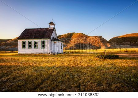 Summer sunset over the old wooden pioneer church in the ghost town of Dorothy in Alberta, Canada.