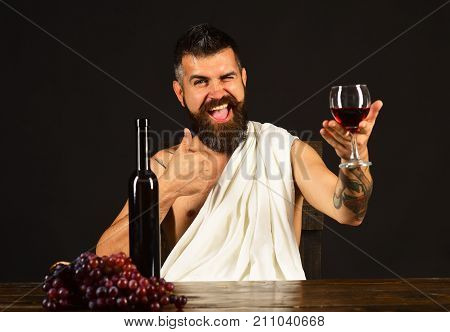 Sommelier tastes drink. Man with beard holds glass of wine on brown background. God Bacchus with happy face wearing white cloth sits by wine bottle and grapes. Viticulture and grape harvest concept