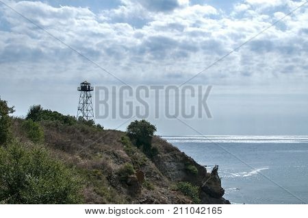 Rocky seashore view with calm sea cloudy sky and watchtower on cliff