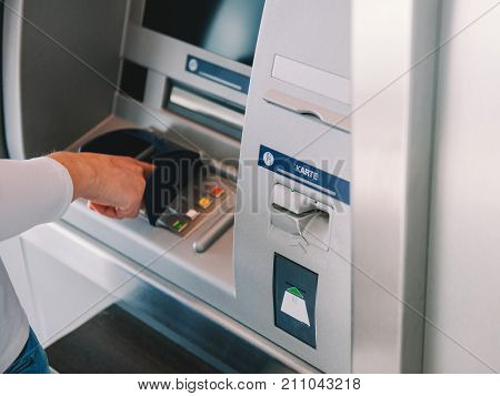 Side view of woman using ATM Automatic Teller Machine cash machine to enter the security PIN and retrieve withdrawal withdrawal money