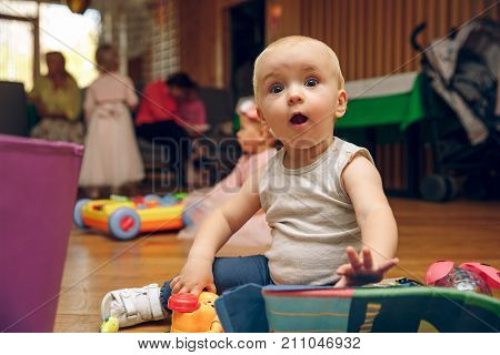 set of crawling babies or toddlers with toys. surprised child plays with toys at home