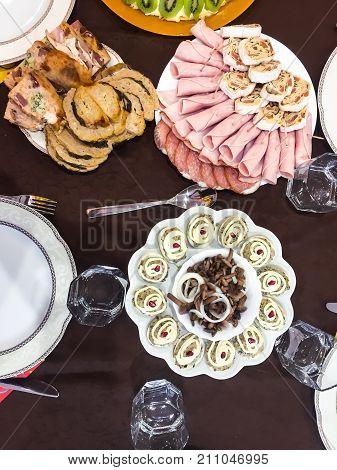 Marinated mushrooms, stuffed eggs, rolls of ham, stuffed chicken- holiday family dinner. Studio Photo