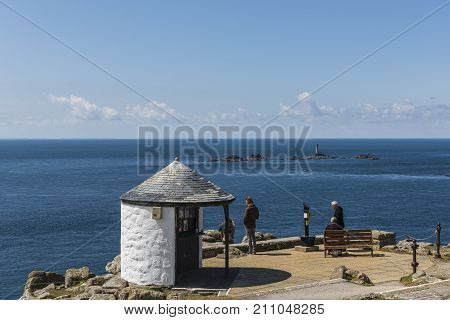Lands' End England - April 27 2017: View people at Lands' End with ocean and old lighthouse.