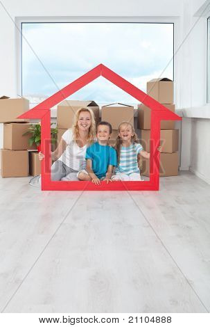 New home concept with happy people among cardboard boxes holding house shaped frame