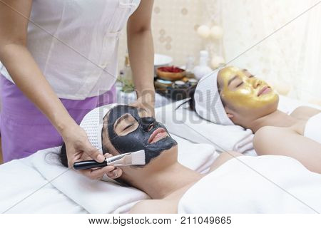 Beautiful smiling young Asian women having mud mask and high quality authentic pure gold facial mask lying on massage table in spa salon