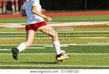 A female high school soccer player dirbbles a ball down the field while racing toward the goal.