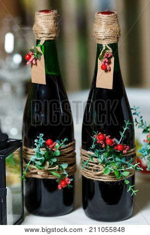 Two green wedding bottles with red wine decorated with flowers greenery and twine